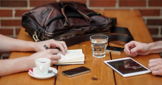 image of a two set of hands in a wooden table with coffee, glass of water, gadgets and a bag around them