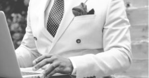 a black and white image of man in suit using a laptop