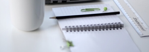 image of a notebook, a pen, paper clips, ruler and a white mug on top of a table