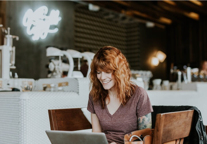 image of a pretty girl with tattoos on her left arm, ginger hair, casual shirt, in a restaurant, smiling while using her laptop