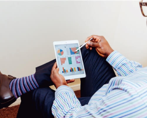 photo of a man using his smart tablet to create performance charts